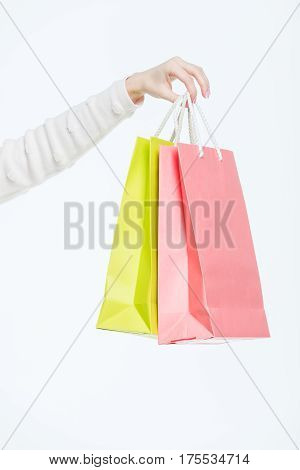 Close-up partial view of woman holding shopping bags