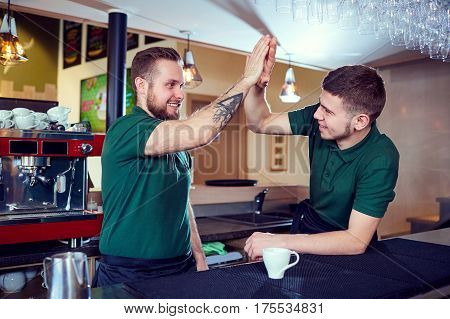 The barista barman team is a waiter at the bar restaurant cafe. OK.