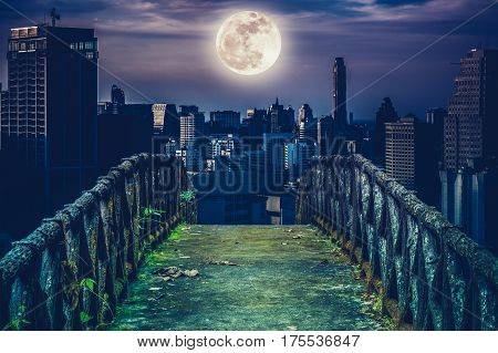 Old concrete bridge with wooden across to skyscrapers with super moon background at night. Dark tone and high contrast style. Cross process style. The moon were NOT furnished by NASA.