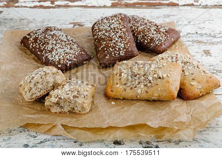 variety of small breads with seeds on grille