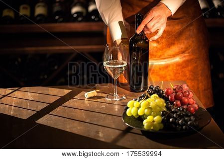 Sommelier standing behind the table with glass, bottle of wine and fruits on it. Wine vault.