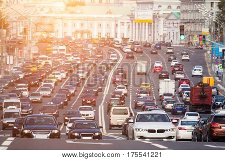 View from above to the heavy traffic on the city highway with warm sunlight