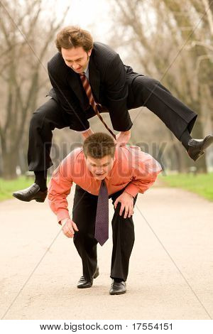 Two businessmen  jumping, playing leapfrog