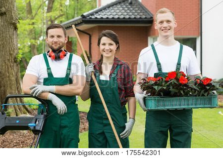 Gardeners With Gardening Tools And Flowers
