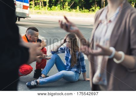 Young victim of car crash sitting on a road with paramedic helping her