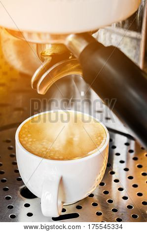 Professional coffee machine making espresso in a cafe with smoke and lighting.