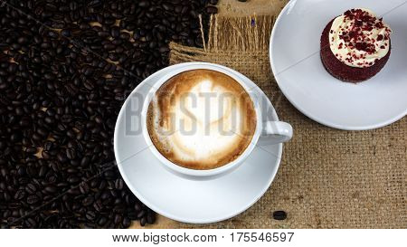 Cappuccino coffee and sweet chocolate red well wet cake. A cup of latte, cappuccino or espresso coffee with milk put on a wood table with dark roasting coffee beans. Drawing the foam milk on top.