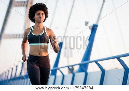 Sportive african american woman running on city bridge