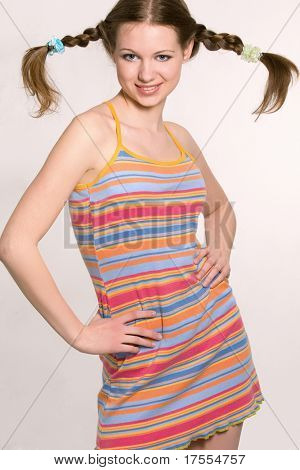 Sexy model with pigtails dressed rainbow-colored short dress