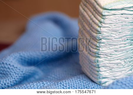 Stack of diapers or nappies on blue knitted blanket closeup