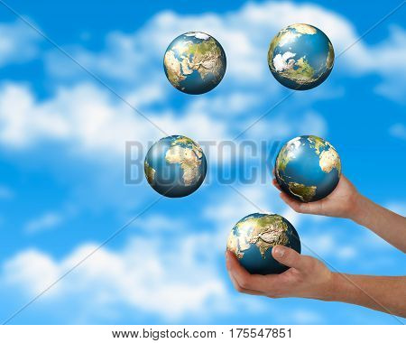 The hands of a man juggling planets. The background of blue sky