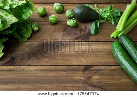 Products containing folic acid - B9 vitamin . Green vegetables on dark wooden background. Celery, avocado, Brussels sprouts, basil, cucumber romaine salad. space for text