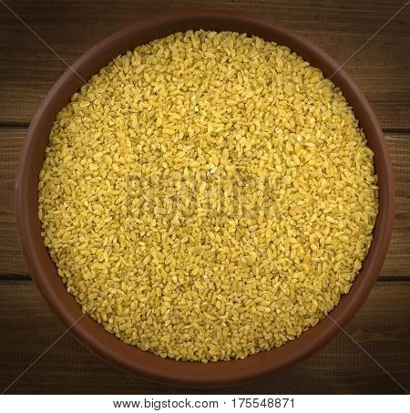 Dry bulgur wheat in a clay bowl on the table