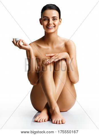 Naked smiling woman applying moisturizer cream sitting on white background. Photo of beautiful young woman with perfect skin. Skin care concept