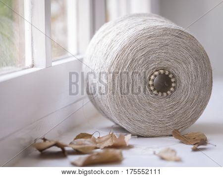 Bobina de hilo Industrial sobre tela textil y hojas secas