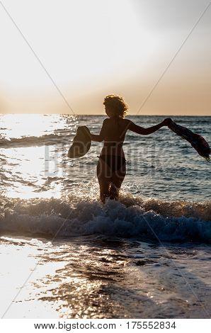 An attractive girl joyfully enters the sunlit sea