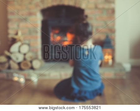 Little Girl Sitting In Front Of The Fireplace