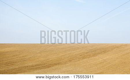 Agricultural landscape. Blue sky and ploughed field in spring prepared for sowing.