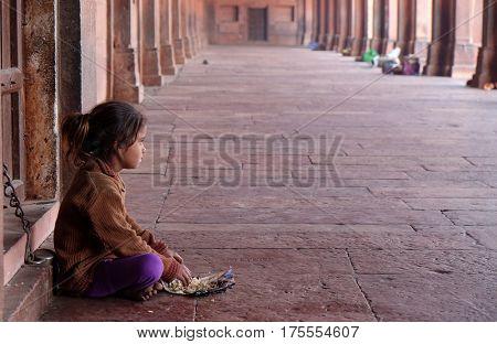 FATEHPUR SIKRI, INDIA - FEBRUARY 15: A poor girl eating in Fatehpur Sikri complex, Uttar Pradesh, India on February 15, 2016.