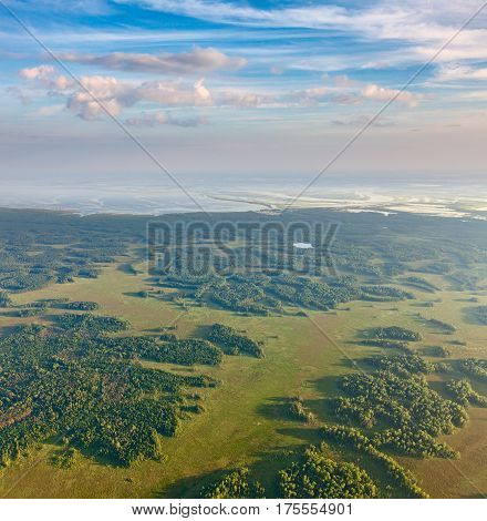 Aerial view over forest beside great river in flood period.