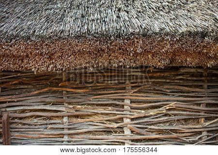 Wattle wall of the shed with straw-thatched roof. Old traditional Ukrainian architecture.