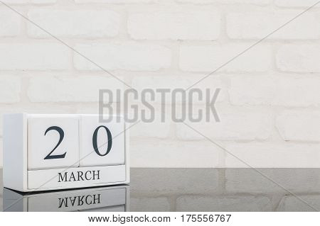 Closeup white wooden calendar with black 20 march word on black glass table and white brick wall textured background with copy space selective focus at the calendar