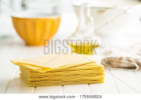 Raw lasagne sheets on white table.