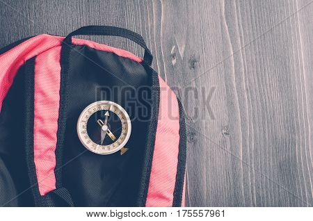 Old Compass And A Backpack On A Dark Wooden Background