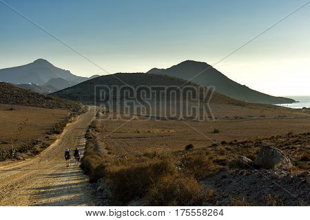 Andalusian landscape: 2 girls with backpack running through the picturesque landscape of Cabo de Gata
