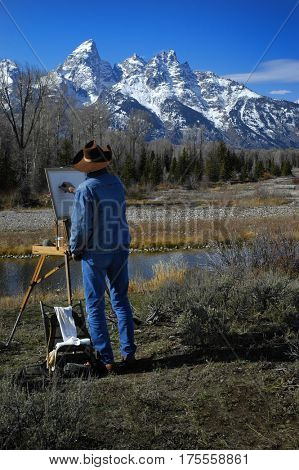 Artist with easle painting Teton Mountain Range in Wyoming