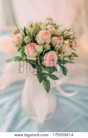 On a light background a tender bouquet of pink roses in a vase