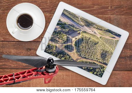 aerial landscape photography concept - reviewing aerial pictures of  North Sand Hills, Colorado,  on a digital tablet with a drone rotor in foreground, screen picture copyright by the photographer