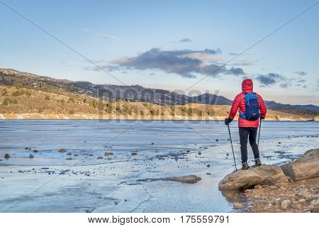 male hiker at a shore of frozen Horsetooth Reservoir near Fort Collins, Colorado - winter hiking concept