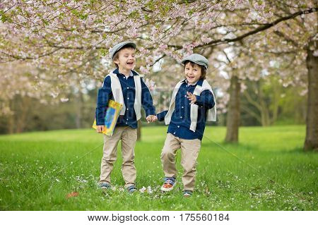 Two Cute Children, Boy Brothers, Walking In A Spring Cherry Blossom Garden