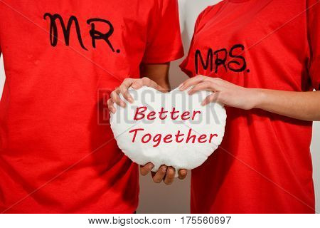 Young Couple In Red Shirts Holding White Fabric Heart With Text