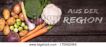 panorama of various vegetables on a rustic wooden background with german text aus der region which means regional vegetables