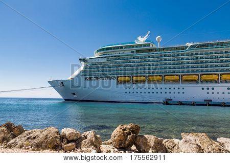 Luxury Cruise ship moored in harbor beyond rock seawall on Curacao