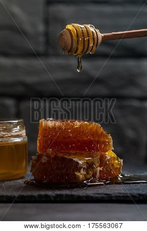 Honey dripping from a wooden honey dipper on the honeycomb on dark background