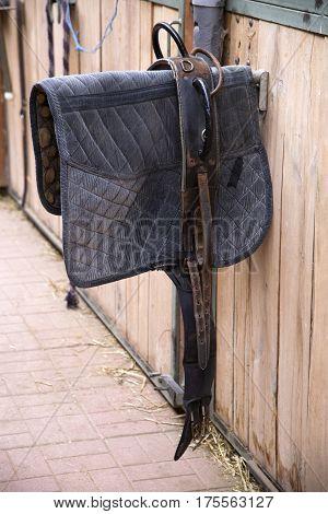 Sporty saddle blanket hanging in a rural barn
