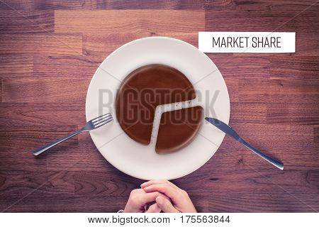 Market share - marketing business concept. Business visual metaphor - businessman with plate and pie chart with imitation of a chocolate cake and snippet with text Market Share.