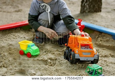 Walks for children in the fresh air. Part of the image of a small child who sits in the sandbox and playing with toy construction vehicles.