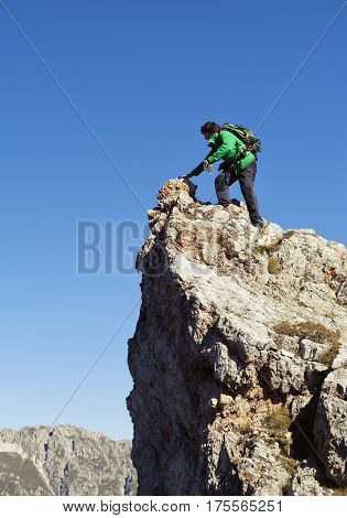 Young backpacker sitting on the edge of a cliff