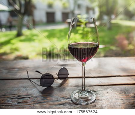 View at the glass of wine infront of the summer yard