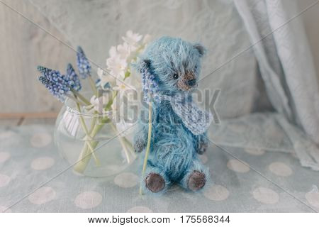 Blue teddy bear with round glass vase with flowers