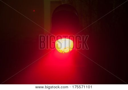 Semaphore on the railway in the fog at night, glowing red. Gloomy scene