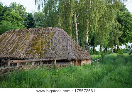 Old wooden shed with moss-grown straw-thatched roof from the Museum of Folk Architecture and Life of Ukraine in Pyrohiv near Kyiv.