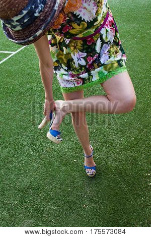 Woman on the soccer field taking off (or putting on) the high heel sandals.