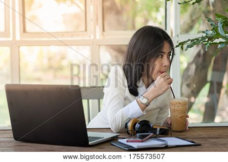 Young Asian woman freelance worker taking a break by sipping iced coffee while working with laptop computer in coffee shop. Startup business and self-employed activity concept