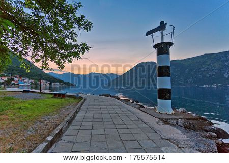Striped beacon on the coast of Bay of Kotor at sunset background. Montenegro
