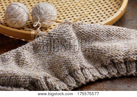 Knitting needles with unfinished hat on a rustic table